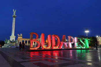 """installation of the word """"Budapest"""" in the red, white and green, at Millenial monument in the background"""