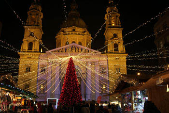 front view of the Basilica at night with a red-lighted Christmas tree on the square