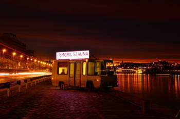 a wooden sauna cabine written Moile Sauna on its top, at night on the Danube bank