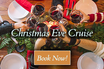 5 people clink with glasses of red wine over a dinner table with pine decor